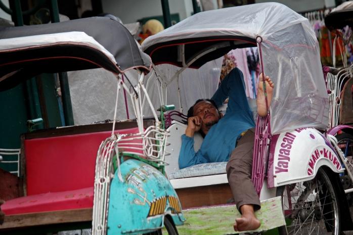 Tukang becak tidur di atas becaknya saat menunggu penumpang di Jalan Malioboro, Yogyakarta, Senin (26/1)